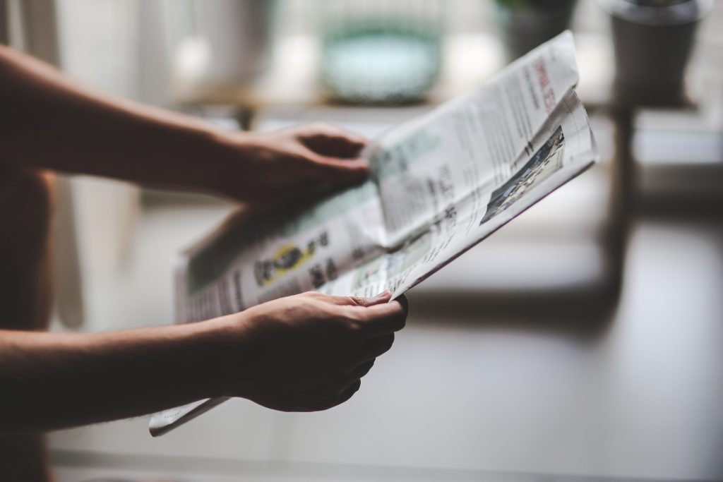hands holding news paper