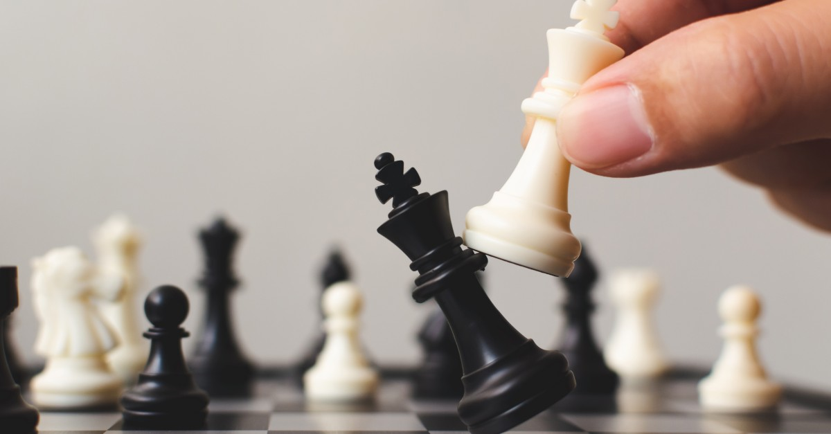 Hand of player chess board game putting white pawn. Sales readiness plan leading to success.
