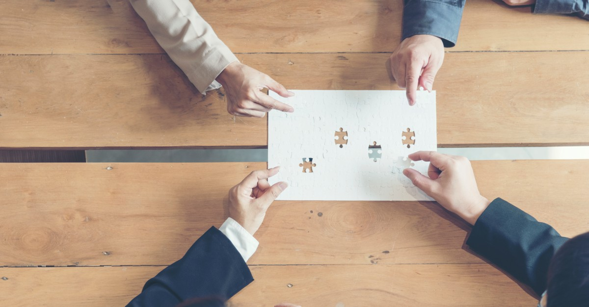 Hands of stakeholder personas holding jigsaw puzzle