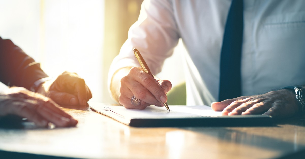 Businessman signing a document about how to close deals effectively.
